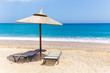 Reed beach umbrella with two loungers on sandy beach at sea