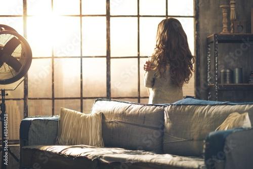 Fotografía  Brunette looking out of urban loft window