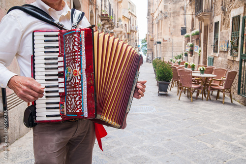 Photo Accordion musician playing on alley of oldSyracuse, Sicily, Italy