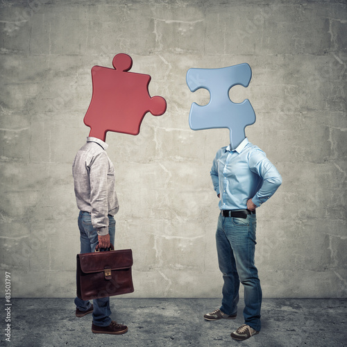 Photo abstract and conceptual image, two people with puzzle-shaped heads discover that they have affinity