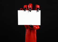 Red Devil Hand With Black Nails Holding A Blank White Card