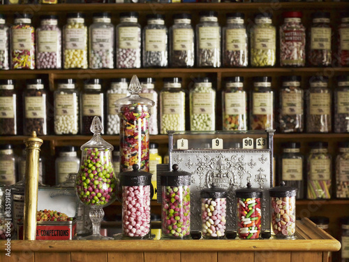 Traditional sweets displayed in tall glass jars on the shelves of a sweet shop.