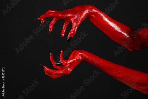 Red Devil's hands, red hands of Satan, black background isolated Fototapeta