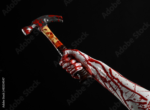 bloody hand holding bloody hammer isolated on black background Canvas Print