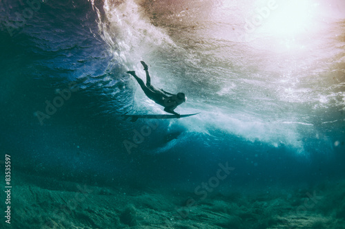 Duckdive surfer and sun reflection under water #83535597