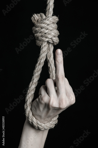 human hand hanging on rope loop on a black background плакат