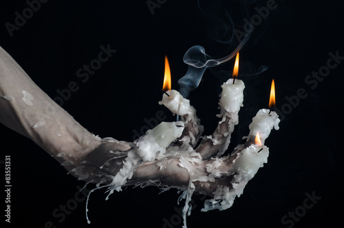Obraz na plátně  on the hand wearing a candle and dripping melted wax studio