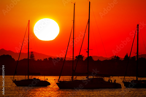 Silhouettes of sailing boats at red and orange sunset