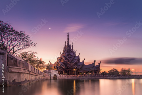 Poster Monument Sanctuary of Truth, Wooden temple construction at sunset in Thai