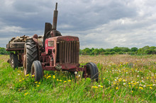 Old Abandoned Red Tractor On A Farm In Field