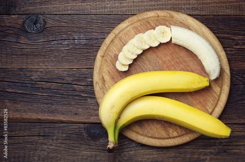 Fotografie, Tablou  Ripe bananas and a sliced