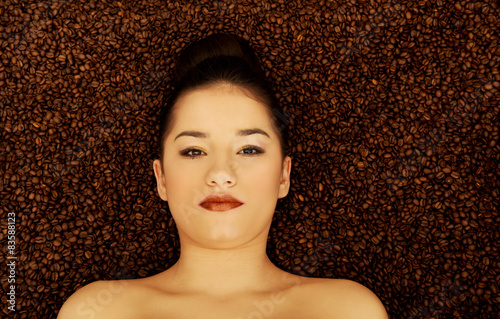 Photo Stands Coffee beans Attractive woman lying in coffee grains.