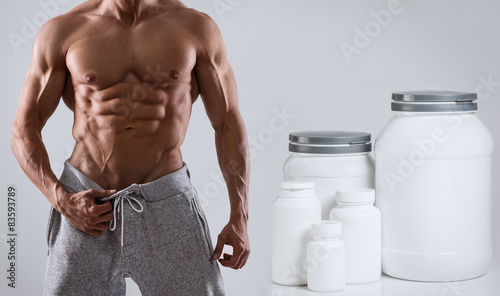 Fotografia  Muscular male torso and food supplements