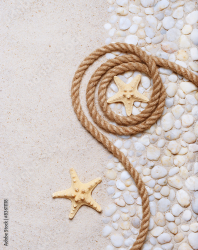 Rope and starfish on the sea pebbles