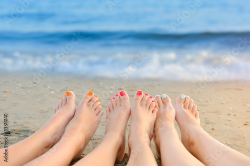 Poster Pedicure Female legs with color pedicure on the background of the sea