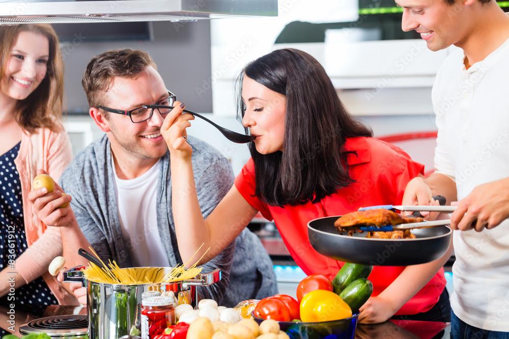 Fotografie, Obraz  Freunde kochen Pasta und Fleisch zuhause in Küche