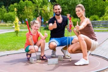FototapetaFamilie spielt draußen zusammen Minigolf