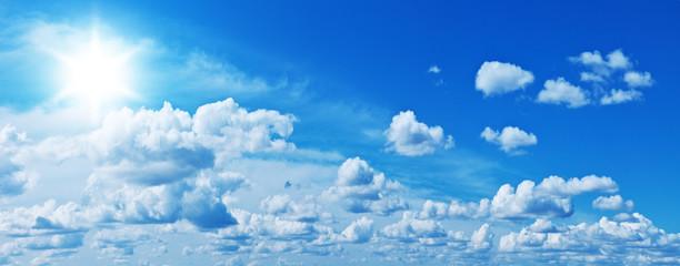 Fototapeta White heap clouds and bright sun in the blue sky.