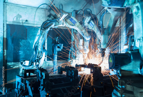 Foto  welding robots  the movement. In the automotive parts industry.