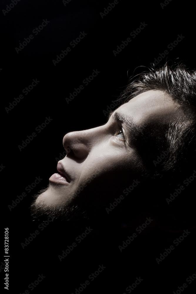 Fototapeta Man side profile portrait looking up lighted on a half face