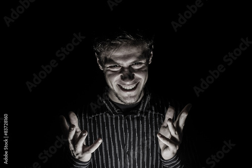 Man portrait with evil look isolated on black background. Fotobehang
