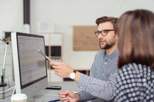 Fotografia  geschäftsmann erklärt seiner kollegin etwas am computer