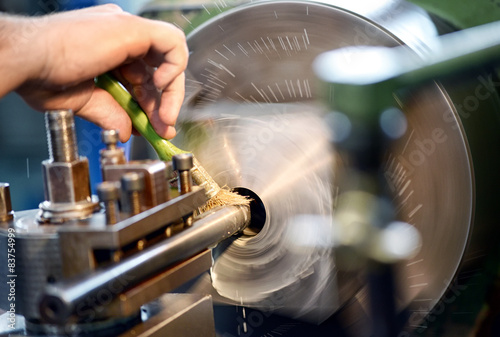 Fotografía  Man placing lubricating oil on a lathe