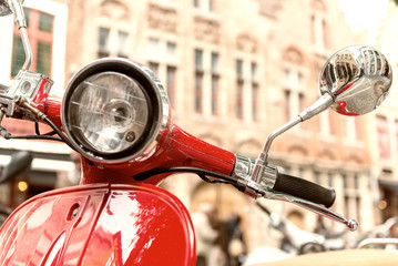 Obraz na Szkle Vintage Old fashioned red motorbike parked in city center