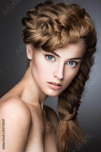 Beautiful girl with light make-up, perfect skin and hairstyle as a braid. Picture taken in the studio on a gray background - 83778347
