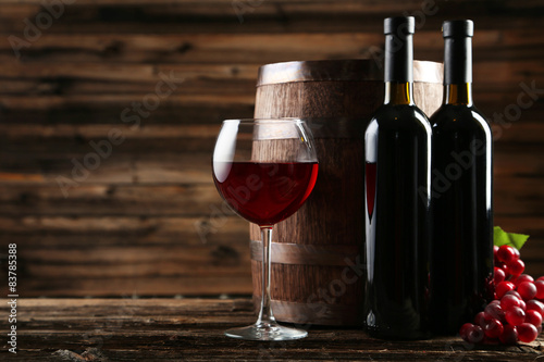 czerwone-wino-w-kieliszku-wraz-z-butelkami-na-brazowym-drewnianym-tle