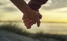 Couple Holding Hands On A Beac...
