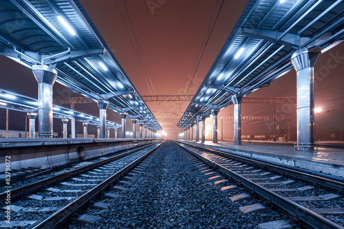 Staande foto Treinstation Railway station at night. Train platform in fog. Railroad
