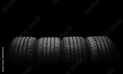 Fotomural four automobile rubber tires isolated on black background