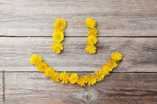 Yellow dandelion on grey wooden background