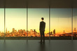 Businessman in empty office stands at the window