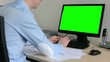 man works on desktop computer in the office - typing on keyboard - green screen