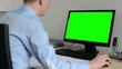 man works on desktop computer in the office - use mouse - green screen