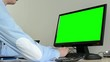 young handsome man sits and works on desktop computer in the office - green screen - closeup