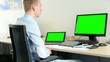 young handsome man sits and looks on desktop and laptop computer in the office - green screen