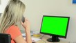 young attractive woman working on the computer in the office and phone - green screen