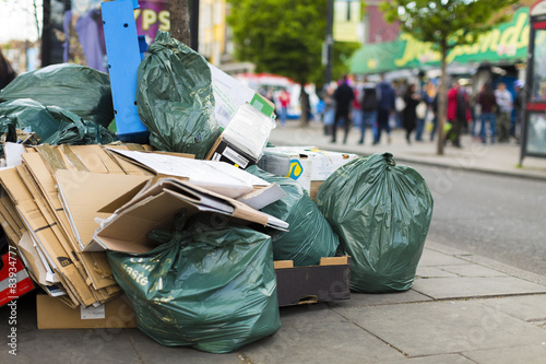Cuadros en Lienzo Basura y bolsas de basura en la acera de una calle concurrida