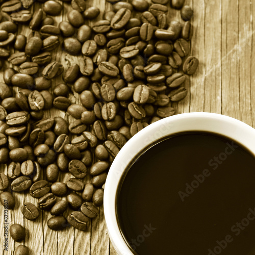 cup of coffee and roasted coffee beans, in sepia toning Poster