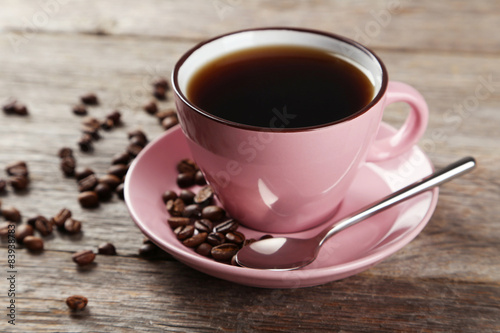 Deurstickers Cafe Cup of coffee with coffee beans on grey wooden background