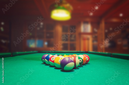 Fotografia Billiard balls on green pool table in bar or pub