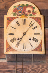 vintage kitchen clock with Roman numbers hanged on wooden backgr