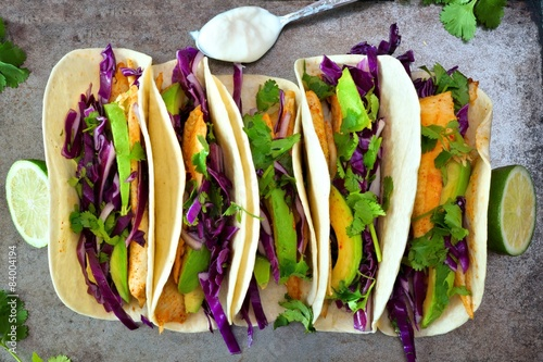 Vászonkép  Fish tacos with red cabbage, avocado and lime on rustic tray