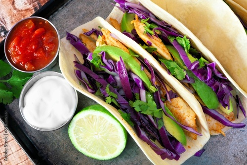 Fényképezés  Fish tacos with red cabbage, avocado and lime on vintage tray