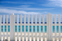 White Fence On The Beach With Blue Sea