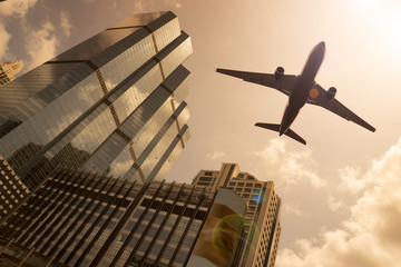 FototapetaAirplane in golden sky with modern buildings