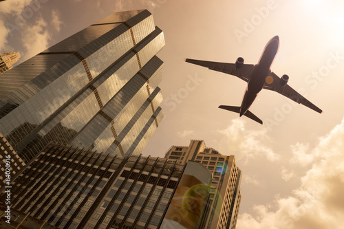 Airplane in golden sky with modern buildings - 84020916